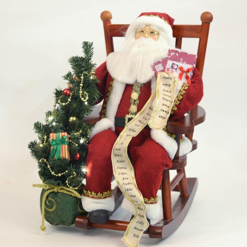 babbo natale seduto su sedia a dondolo con albero di